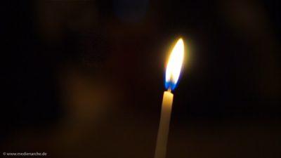 Eine dünne brennende Kerze in einem ansonsten dunklen Raum.