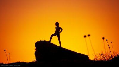 Silhouette eines Kindes vor einem strahlenden Abendhimmel.
