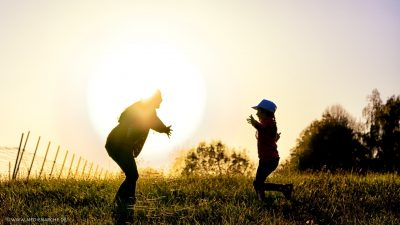 Ein Kind rennt aus dem schattigeren Bereich in die Arme der von der Sonne leuchtenden Mutter.
