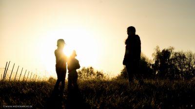 Zwei Kinder vor der untergehenden Sonne im Licht, werden von ihrer Mutter liebevoll betrachtet.