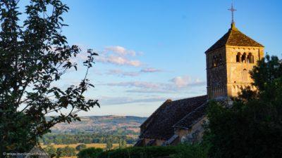 Blick auf ein Tal, im Vordergrund eine alte romanische Kirche auf dem Hügel.