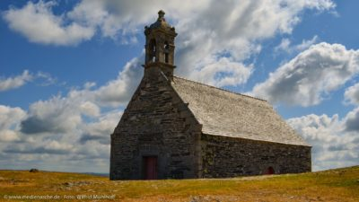 Eine alte Steinkirche, einsam in einer rauhen Berglandschaft