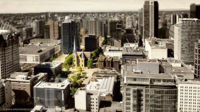 Blick auf eine einladend aussehende Kirche mit Grünflachen, inmitten einer Großstadt mit Wolkenkratzern.