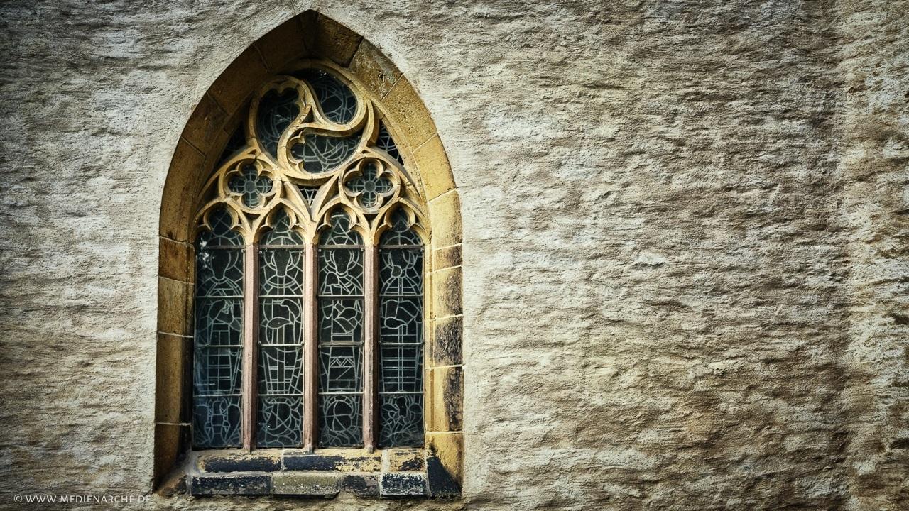 Ein kunstvoll gestaltetes Kirchenfenster mit Verzierungen aus Stein und Glasmosaiken.