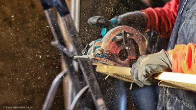 Eine Säge in Betrieb, die ein Stück Holz zersägt, während die Späne fliegen.