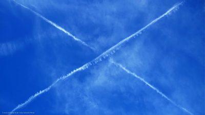 Kondensspuren zweier Flugzeuge zeichnen ein Kreuz am Himmel.