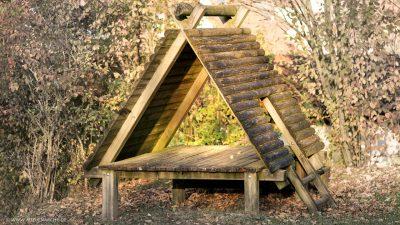 Schlichtes Häuschen auf einem leeren Spielplatz, das inmitten von Herbstlaub steht und innen warm von der Sonne ausgeleuchtet wird.
