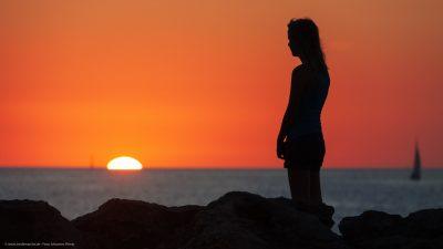 Ein Mädchen, das den Sonnenuntergang am Meer bestaunt.