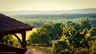 Blick von einer Terasse auf eine hügelige bewaldete Landschaft im Licht der Morgensonne.