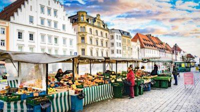 Ein Obst- und Gemüsestand in einer Altstadt. Im Hintergrund Fassaden historischer Gebäude.