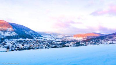 Traumhafter Blick auf ein im Tal gelegenes Örtchen an einem Wintermorgen.