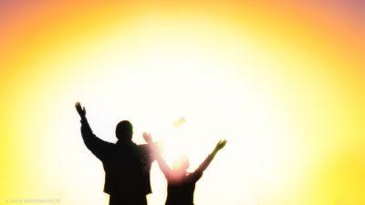Eine Mutter mit ihrem Kind stehen in strahlendem Licht und heben die Hände in Anbetung.