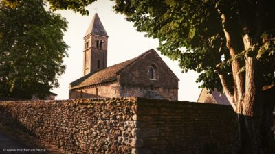 Eine alte Kirche aus Natursteinen, im Vordergrund eine Steinmauer.