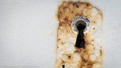 Ein Schlüsselloch an einer alten Tür, um das sich Rost gebildet hat.