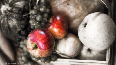 Rot glänzende Äpfel in einem ansonsten entsättigtem Bild auf dem auch weiteres Obst und Gemüse zu sehen ist.