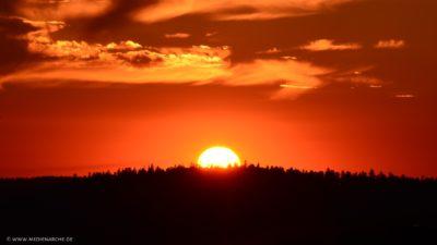 Ein intensiv leuchtender roter Feuerhimmel über einem bewaldeten Hügel.