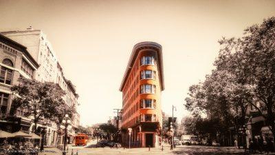Ein rotes Eckhaus an einer Straßenkreuzung, daneben ein roter Tramwaggon. Der Rest des Bildes entsättigt.