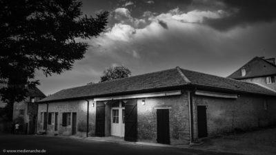 Aufnahme einer alten Scheune. Am Eingang leuchtet ein einladendes Licht, im Hintergrund ein wolkiger Himmel. Schwarz-weiß Fotografie.