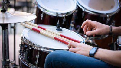 Hände eines Schlagzeugers am Drumset, bereit zum Einsatz.