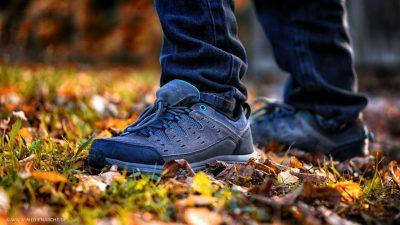 Nahaufnahme der Füße eines jungen Mannes, auf einer von Herbstblättern bedeckten Wiese.