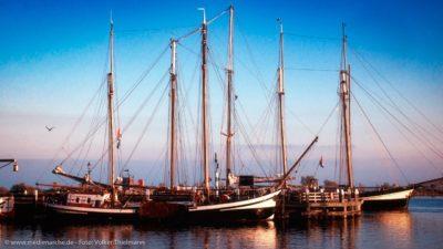 Einige am Pier vertaute Segelboote, angeleuchtet von der Morgensonne.