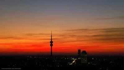 Silhouette eines Sendemasts und einiger Hochhäuser im Abendlicht.