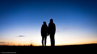 Zwei Silhouetten vor dem Licht der aufgehenden Sonne am Morgen.