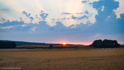 Aufgehende Sonne, die kurz zu sehen ist, bevor sie von Wolken verdeckt wird.