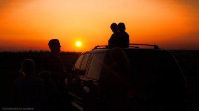 Eine Familie, die den Sonnenuntergang bestaunt.