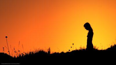 Eine Mädchensilhouette vor einem orange-gelben Himmel.