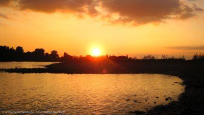 Stimmungsvolles Bild der untegehenden Sonne am Flussufer