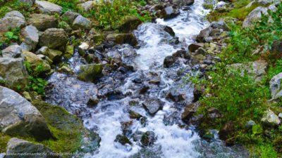 Ein Bergbach der eine Steinkaskade herunterfließt. Schäumendes Wasser.