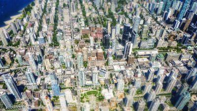 Blick von weit oben auf ein Stadtzentrum mit vielen Hochhäusern deren Glasfassaden blau schimmern. Miniatur-Effekt.