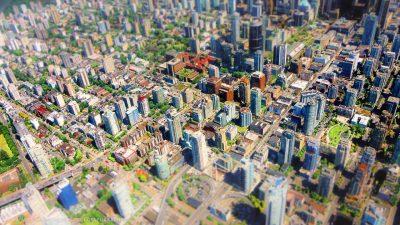 Blick von weit oben auf ein Stadtzentrum mit Hochhäusern und vielen grünen Flächen. Miniatur-Effekt.