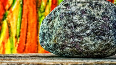 Ein großer Stein auf einem felsigen Untergrund, der den Blick auf ein leuchtendes, warmes Bild versperrt.