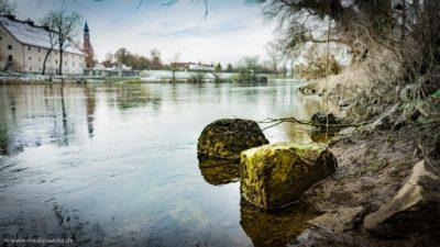 Mit Moos bewachsene Steine an einem Flussufer. Im Hintergrund einige Gebäude und eine Kirche.