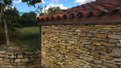 Ein aus Natursteinen gebautes Haus, mit niedrigem Ziegeldach. Daneben schließt sich eine Weide an.