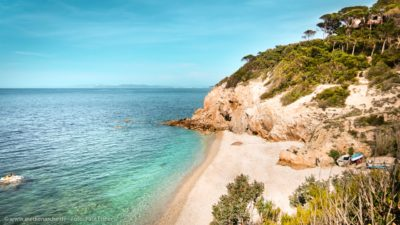 Ein kleiner Strand, umgeben von Felsen. Azurblaues Wasser und hellblauer Himmel.