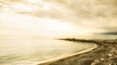 Ein einsamer Strand vor einem glühenden Abendhimmel.
