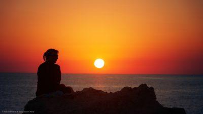 Eine Frau, auf ein weites Meer blickend. Die untergehende Sonne im Hintergrund.