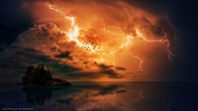 Eine Szene, wie aus einem Traum. Gewitterwolken und Blitze im Hintergrund. Im Vordergrund ein Vogelschwarm über dem Meer.