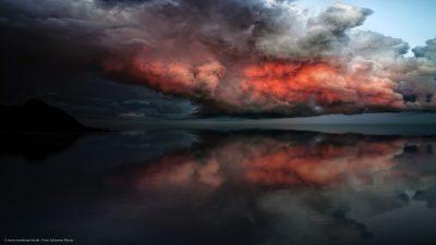 Eine Szene, wie aus einem Traum. Gewitterwolken über einer glatten Meeresoberfläche.