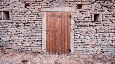 Eine Holztür in einem Steinhaus, mit einem verschlossenen Riegel davor.