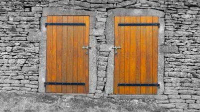 Zwei Holztüren in einem Steinhaus, mit einem verschlossenen Riegel davor.