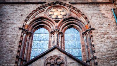 Ein verziertes Kirchenfenster an einer alten Kirche mit Glasmosaik und kunstvollen Steinarbeiten.