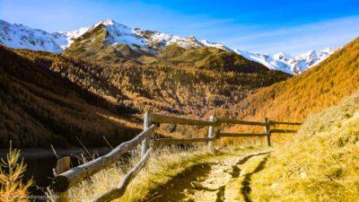 Ein Wanderweg in den Bergen. Schneebedeckte Bergspitzen im Hintergrund.