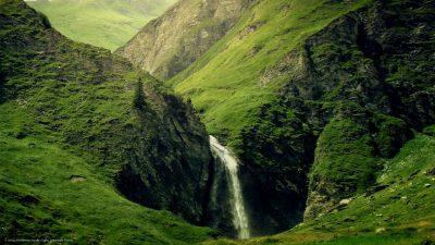 Ein Wasserfall inmitten von rauhen Berghängen.