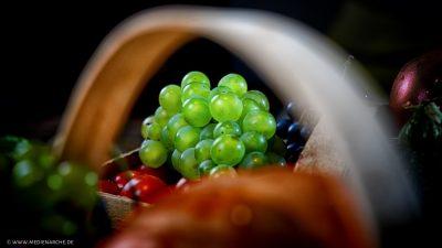 Leuchtende, frische Weintrauben in einem Korb mit weiterem Obst und Gemüse.