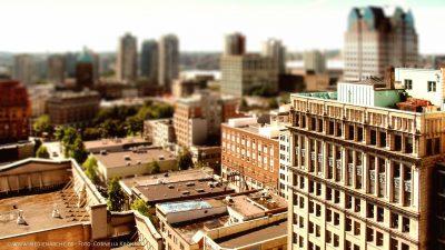 Aufnahme eines Häuserblocks in einer Großstadt. Im Hintergrund sind die Wolkenkratzer der Downtown erkennbar. Miniatur-Effekt.