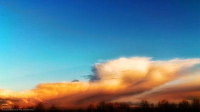 Wolkenformation am Horizont, mit strahlend blauem Himmel darüber.
